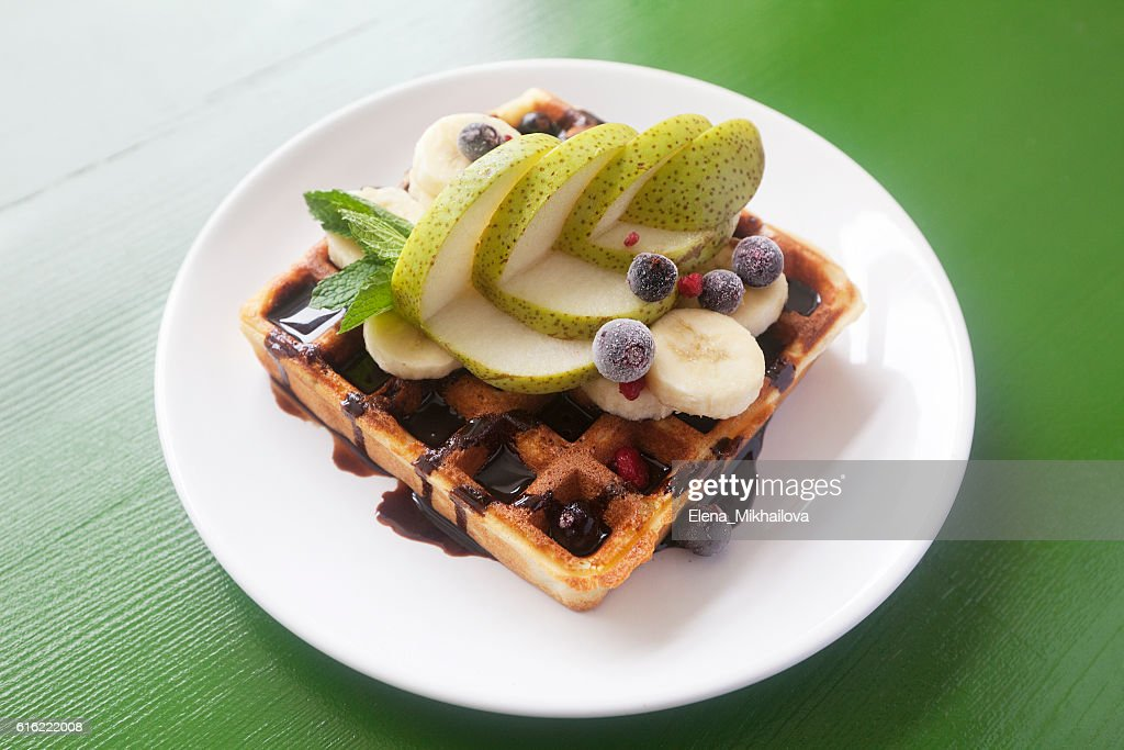 Wafers with chocolate, banana, a pear, berries and mint : Stockfoto