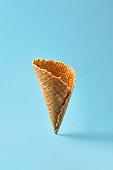 Waffle cornet on light blue background. Summer Food concept.