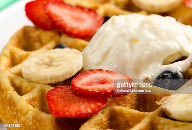 Waffle with fruit A waffle topped with whipped cream blueberries sliced strawberries and sliced bananas It is photographed from close up