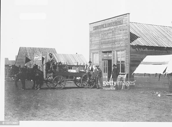A wagon is loaded with furniture ouside of the Furniture and Undertaking business Broadway Street Round Pond Oklahoma Territory January 1894