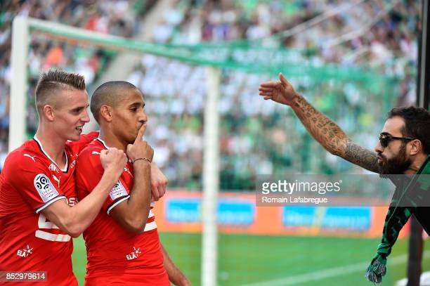 Wahbi Khazri of Rennes and Benjamin Bourigeaud of Rennes react with a SaintEtienne's ultra during the Ligue 1 match between AS SaintEtienne and Stade...