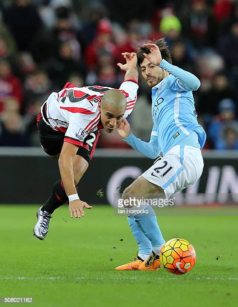 Wahbi Khazri of Sunderland is takled by David Silva of Manchester City during the Barclays Premier League match between Sunderland and Manchester...