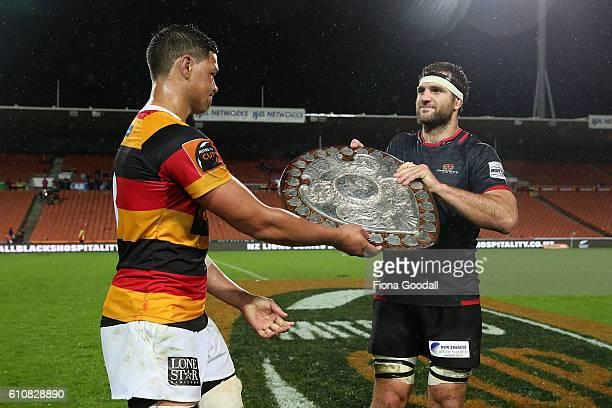 Waikato captain Whetu Douglas hands the Ranfurly Shield to Canterbury captain Luke Whitelock during the round seven Mitre 10 Cup match between...