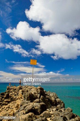 Waimea Bay boulder with warning sign.