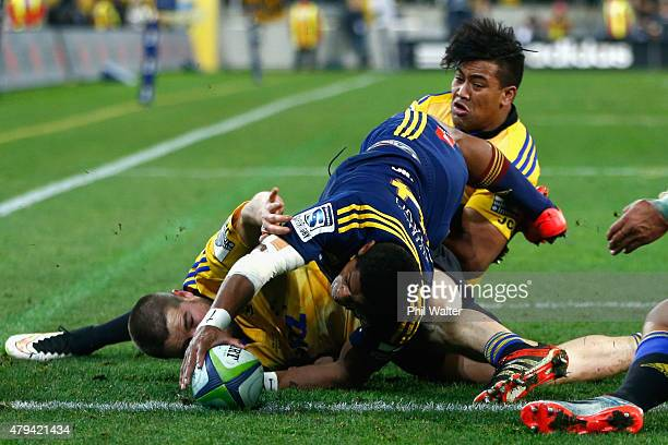 Waisake Naholo of the Highlanders scores a try despite the tackles of Dane Coles and Julian Savea of the Hurricanes during the Super Rugby Final...