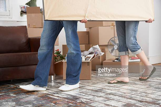 Waist down man and woman carrying picture in home with cardboard boxes