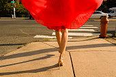 Waist down shot of young woman strolling along sidewalk wearing flowing red skirt