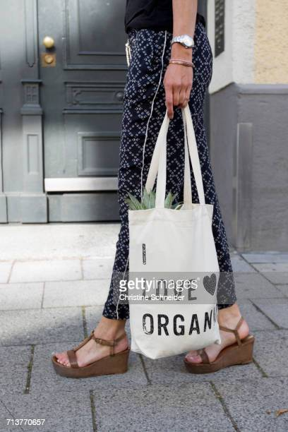 Waist down view of woman strolling on street carrying organic shopping bag