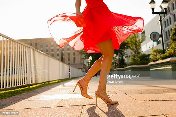 Waist down view of young woman twirling whilst wearing red dress