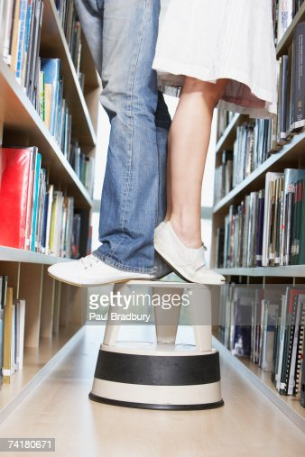 Waist Down Woman And Man Standing On Step Stool In Library