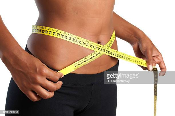 Waist measuring by yellow meter tape.