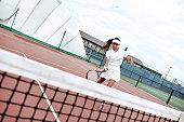 Waist up portrait of positive lady having tennis match on sunny day. She is moving near net and lifting arm with racket for beating ball. Active game as kind of workout concept