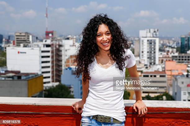 Waist up shot of a young woman with very curly hair on a rooftop in Mexico City