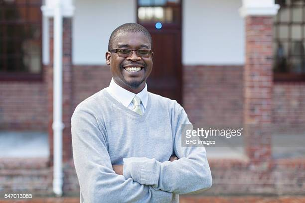 Waist up shot of African male teacher with arms crossed, Cape Town, South Africa