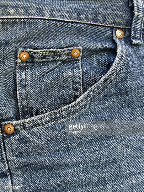 Waistband and pocket close-up on a pair of faded blue jeans
