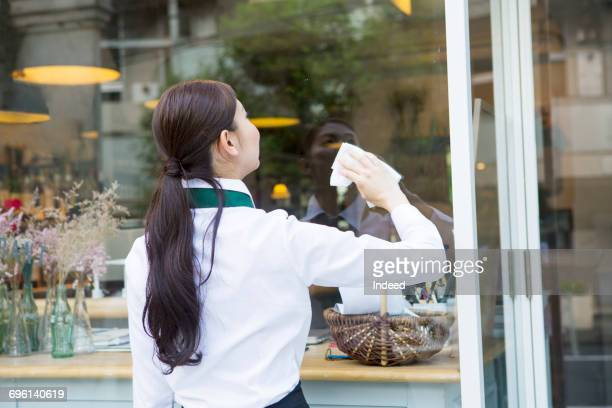 Wait staff cleaning restaurant window