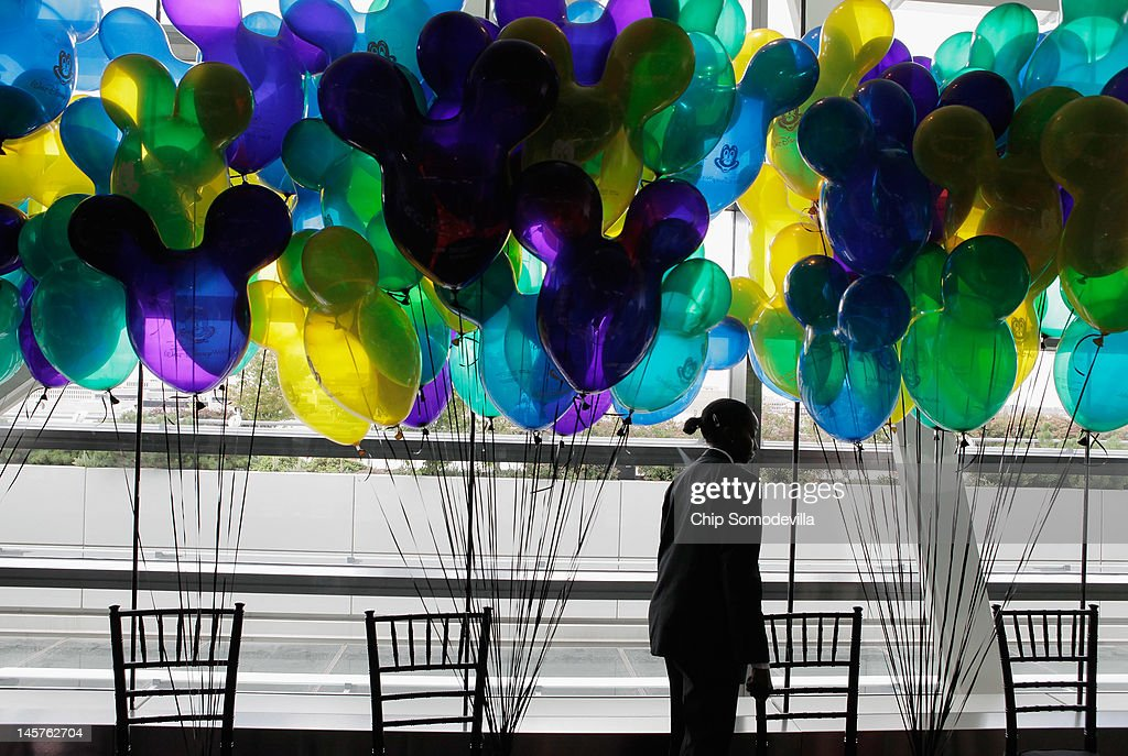 A wait staff member walks past a forrest of balloons during an event introducing The Walt Disney Companys new 'Magic of Healty Living' program at the Newseum June 5, 2012 in Washington, DC. As part of the new healthy eating initiative, all products advertised on Disney's child-focused television channels, radio stations and Web sites must adhear to a new set of strict nutritional standards. Addionally, Disney-licensed products that meet criteria for limited calories, saturated fat, sodium and sugar can display a logo - Mickey Mouse ears and a check mark - on their packaging.