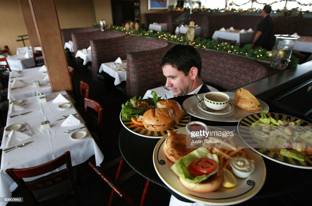 Waiter Alexander Alioto carries a tray of food through an empty dining room at Alioto's Seafood Restaurant December 3, 2008 in San Francisco, California. A report by The Institute for Supply Management says that its services sector index dropped in November to 37.3, down from 44.4 in October, as the service industry struggles through the weak economy.