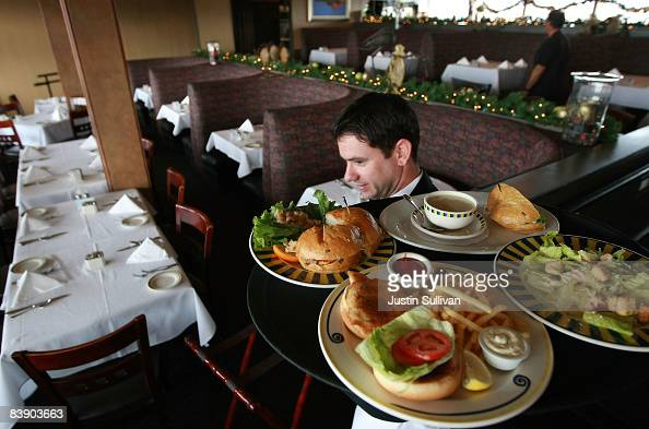 Waiter Alexander Alioto carries a tray of food through an empty dining room at Alioto's Seafood Restaurant December 3 2008 in San Francisco...