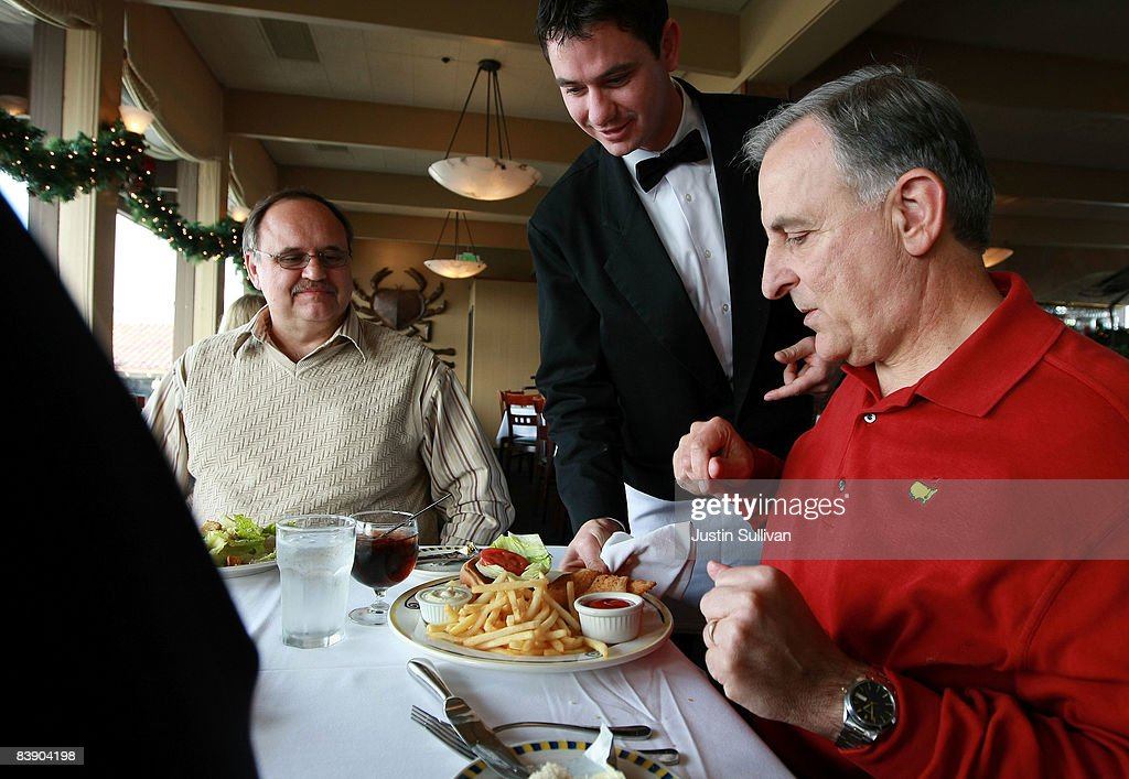 Waiter Alexander Alioto (C) serves lunch customers at Alioto's Seafood Restaurant December 3, 2008 in San Francisco, California. A report by The Institute for Supply Management says that its services sector index dropped in November to 37.3, down from 44.4 in October as the service industry struggles through the weak economy.