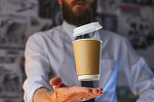 Levitating in the air paper cup with hot coffee. Barista, a bearded young man in a white shirt with a tie, creates miracles - advertises his drink, causing it to soar. Logoplacement concept