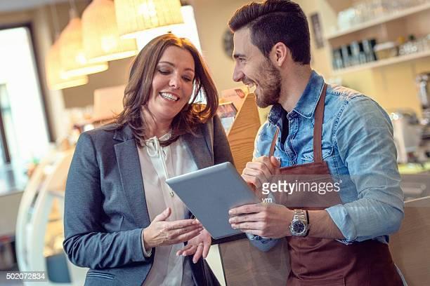 Serveur et client souriant tout en regardant la carte numérique