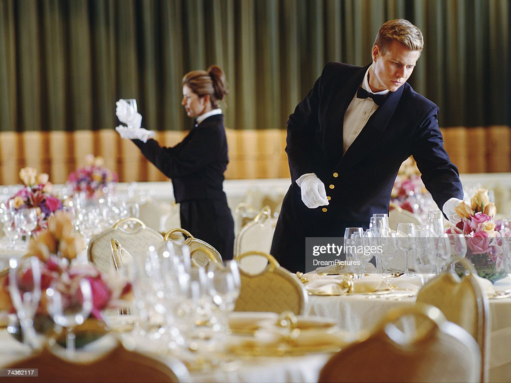 Waiter and waitress arranging tables in restaurant : Stock Photo