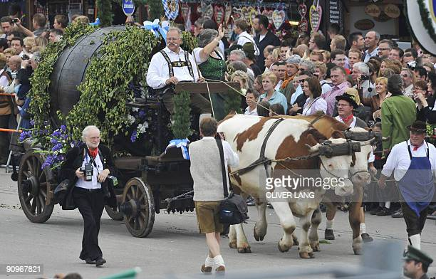 A waiter and waitress of the Oktoberfest beer festival drive a giant beer barrel behind their oxen during the opening parade on September 19 2009 at...
