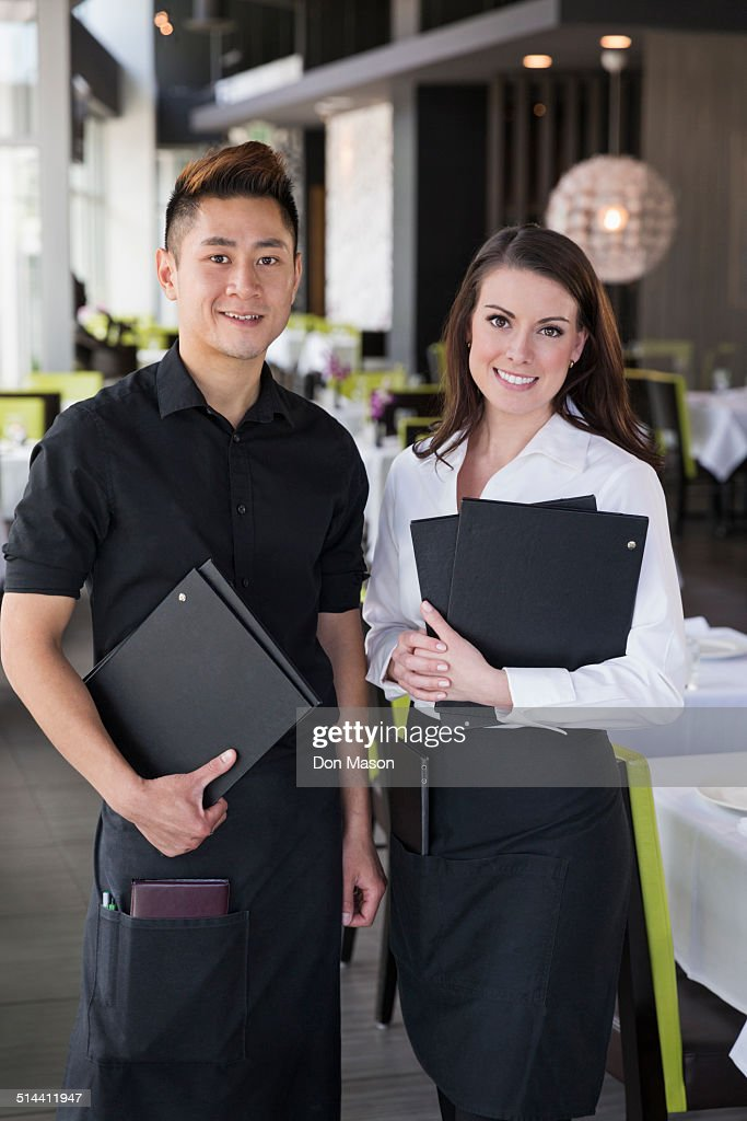 Waiter and waitress smiling together in restaurant