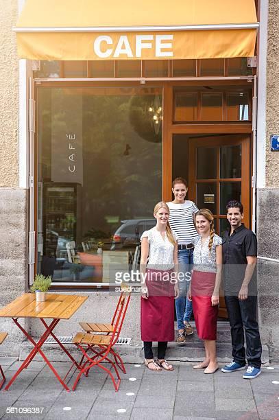 Waiter and waitresses outside cafe, portrait