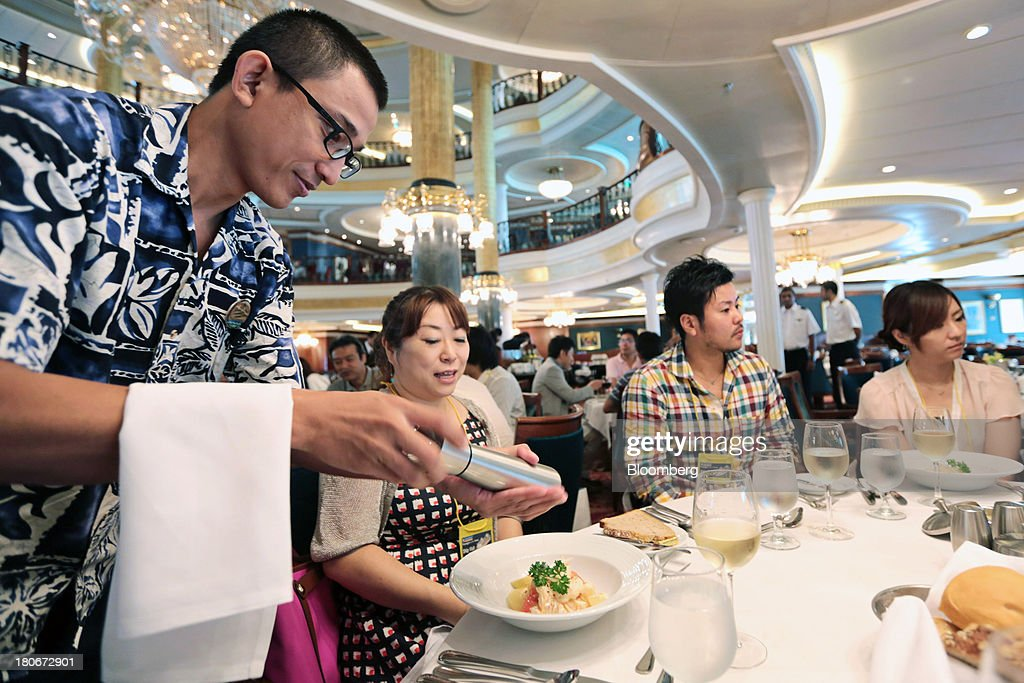 A waiter applies pepper to a woman's lunch in the 'Carmen' dining room aboard the Royal Caribbean Cruises Ltd.'s Voyager of the Seas, berthed at the Ohi wharf in Tokyo, Japan, on Saturday, Sept. 14, 2013. Royal Caribbean, the worlds second-largest cruise-line operator, doubled its dividend and will make directors stand for election every year. Photographer: Yuriko Nakao/Bloomberg via Getty Images