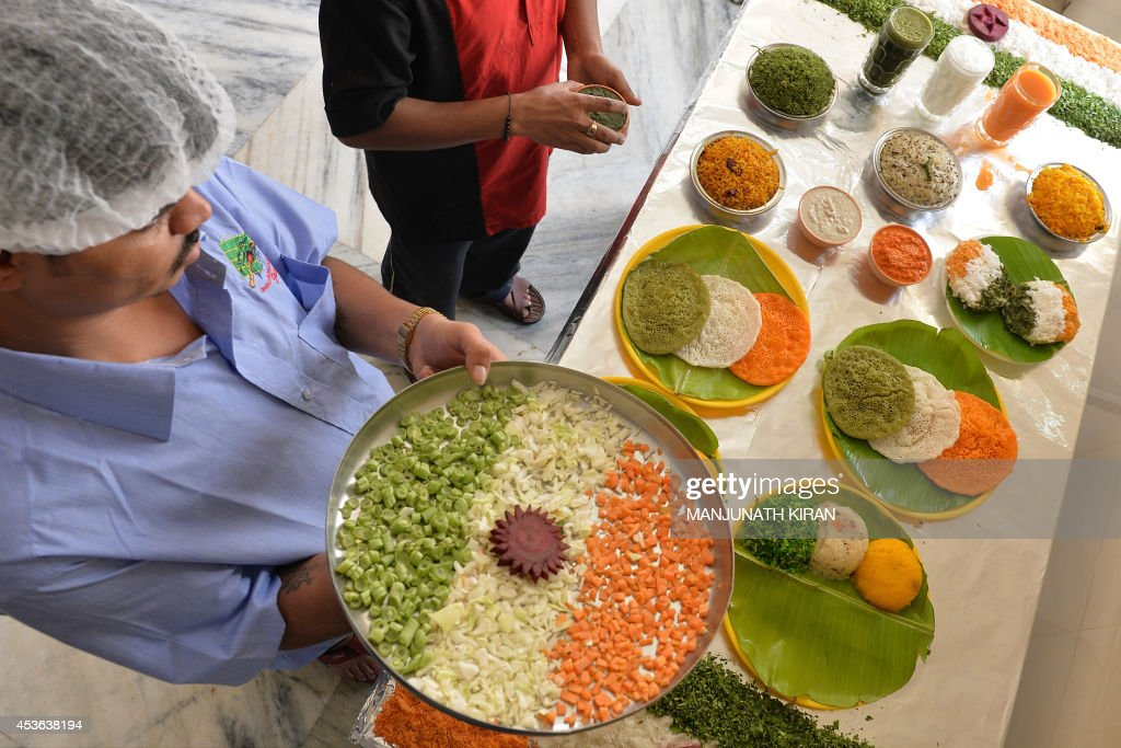 A waiter arranges various food items prepared in the Indian tri-colours at a hotel in Bangalore on August 15, 2014. The hotel management has taken a unique approach to attract customers and also to celebrate the 68th Independence Day by preparing several food dishes in orange, white and green colours which represent the Indian flag. AFP PHOTO/Manjunath KIRAN