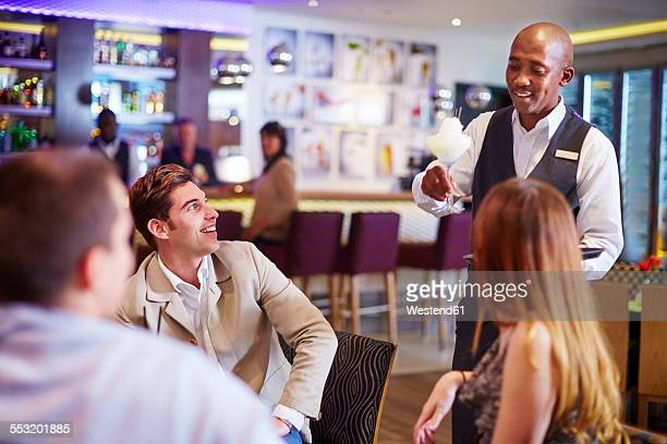 Waiter at hotel bar serving cocktail to business people