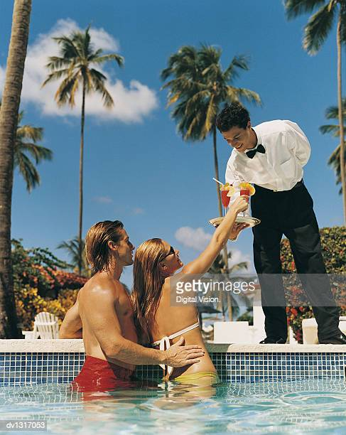 Waiter at the Water's Edge Serving a Couple Cocktails in a Swimming Pool