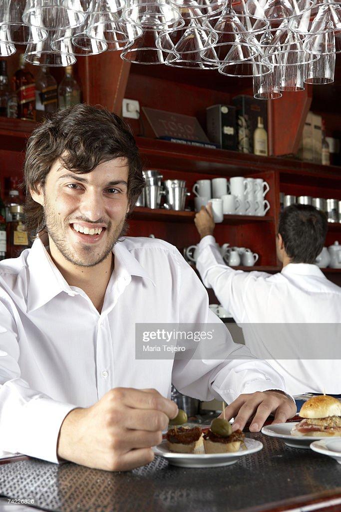 Waiter behind counter in cafe, waist up, portrait : Foto de stock
