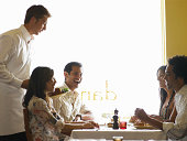 Waiter bringing plates of food to four adults in restaurant, side view