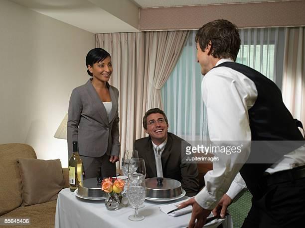 Waiter bringing room service order into hotel room