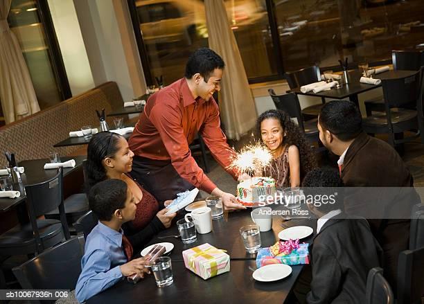 Waiter brings birthday cake for girl (10-11) during dinner