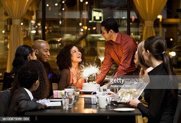 Waiter brings birthday cake for woman during dinner