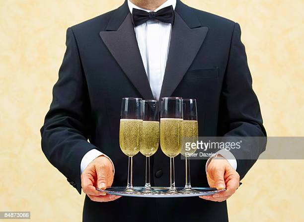 Waiter, butler, with four glasses of Champagne.