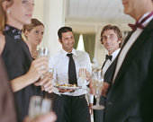 Waiter by people wearing formal attire holding champagne glasses