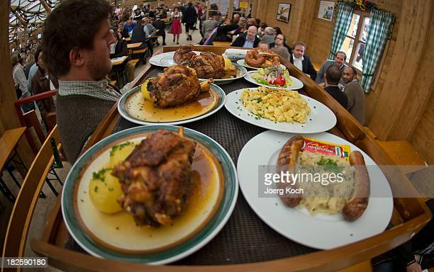 A waiter carries a large tray of meals at the Oktoberfest 2013 beer festival at Theresienwiese on October 1 2013 in Munich Germany This year some...