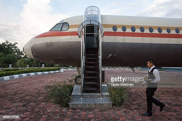 A waiter carries a mug of beer to a customer waiting in Flight Cafe a restaurant inside a disused airplane on August 13 2015 in Naypyitaw Burma The...