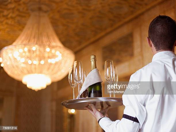 Waiter carrying Champagne on tray in hotel, rear view