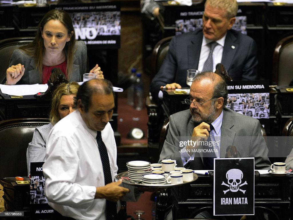 A waiter carrying cups of coffee passes by opposition deputies in one of whose desks there is a sign that reads 'Iran Kills' at the chamber of deputies in Buenos Aires on February 27, 2013, as they discuss the possibility of an agreement with Iran to establish a truth commission over a terrorist attack that took place in 1994. Eight Iranian nationals are still wanted in connection with the bombing of the Argentine Israelite Mutual Association (AMIA) that left a toll of 85 dead and 300 wounded. AFP PHOTO/Juan Mabromata