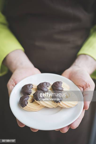 Waiter carrying plate of biscuits