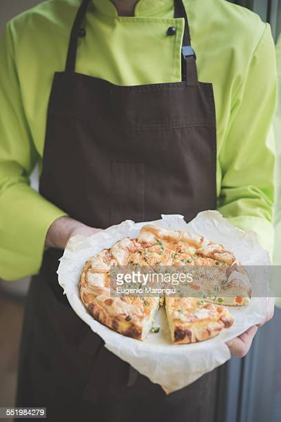 Waiter carrying plate of frittata