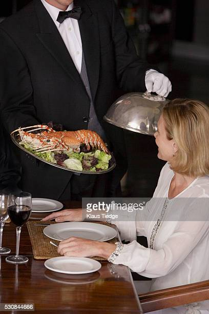 Waiter carrying serving plate with lobster