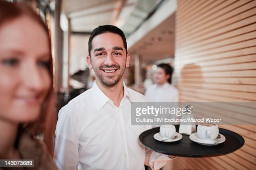 Waiter carrying tray in cafe : Stock Photo