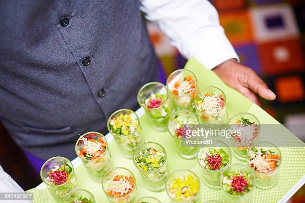 Waiter carrying tray of individual salads in glasses